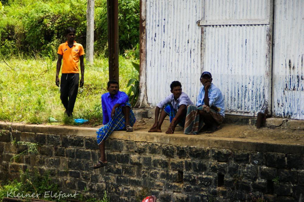 Vier Männer am Bahngleis in Sri Lanka