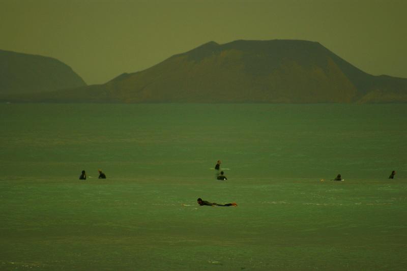 Surfer in Famara, im Hintergrund La Graciosa.